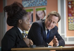 Prime Minister David Cameron watches as Tino Muchirawehondo, 15, solves a problem in her year 11 maths class in Cedar Mount high school in Gorton, Manchester.
